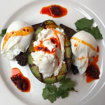 Grilled avocado with poached eggs, fresh cheese, and spicy sauce